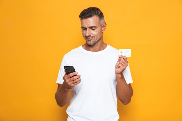 Portrait of european guy 30s in white t-shirt holding mobile phone and credit card isolated on yellow