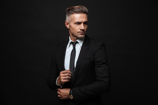 Portrait of european handsome businessman dressed in formal suit posing and looking aside isolated over black wall