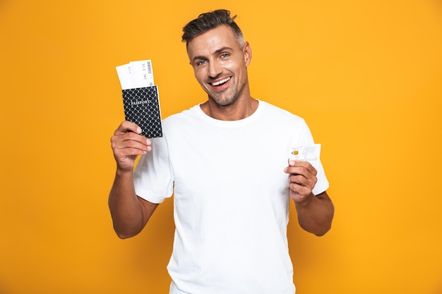 Portrait of european man 30s in white t-shirt holding credit card and travel tickets isolated on yellow