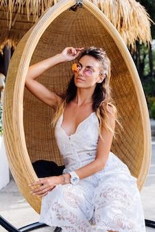 Ritratto di donna romantica europea in abito estivo bianco fuori dalla località di soggiorno dell'hotel in sedia di paglia di uovo.