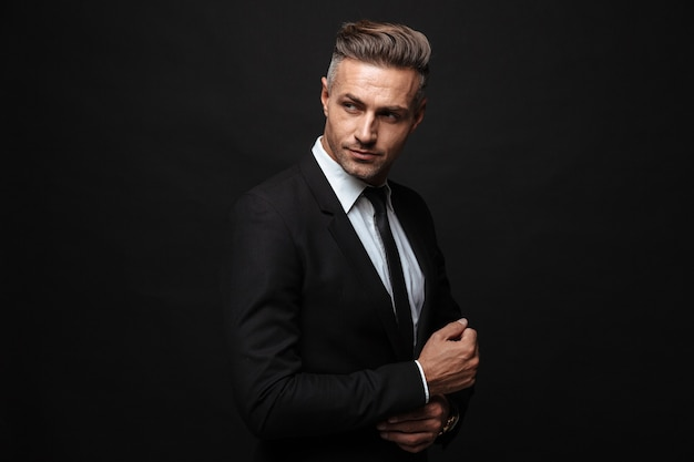 Portrait of european unshaven businessman dressed in formal suit posing and looking aside isolated over black wall