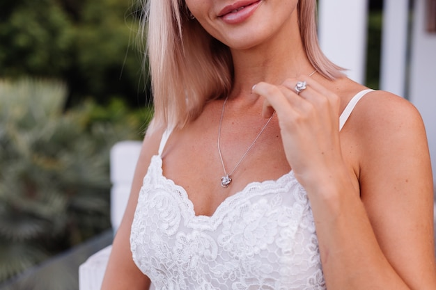 Portrait of european woman in wedding dress wearing necklace and ring.