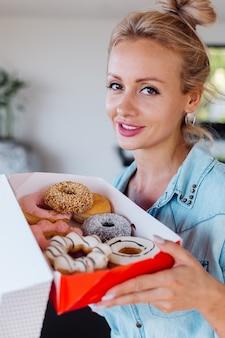 Ritratto di donna europea con capelli biondi godendo di ciambelle in cucina a casa villa.