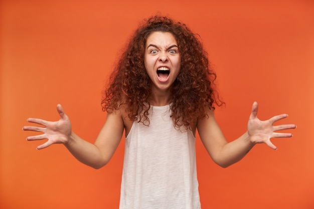 Portrait of evil, adult redhead girl with curly hair. wearing white off-shoulder blouse. trying to scare you. screams and spreading her arms. isolated over orange wall
