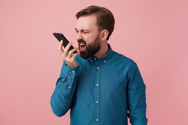 Ritratto di un malvagio giovane barbuto, che indossa una camicia di jeans, che grida al telefono, scherza con qualcuno isolato su sfondo rosa con copia spazio.