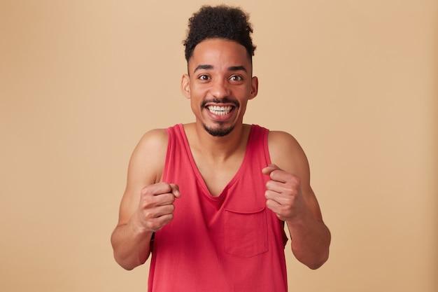 Ritratto di maschio eccitato, afroamericano con acconciatura afro. indossare canottiera rossa. stringendo i pugni, sospeso sul muro beige pastello