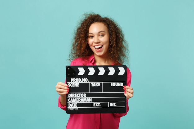 Portrait of excited african girl in casual clothes holding classic black film making clapperboard isolated on blue turquoise background. people sincere emotions, lifestyle concept. mock up copy space.