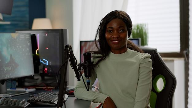 Ritratto di eccitato giocatore di streamer professionista africano che guarda l'obbiettivo sorridente. cibernetica in streaming online durante il torneo di videogiochi in casa con luci al neon, campionato virale