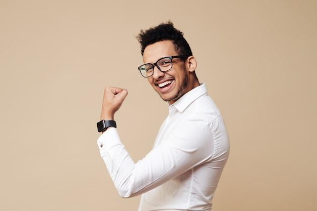 Ritratto di un eccitato uomo afro in piedi con le mani alzate e guardando la parte anteriore isolata su un muro beige che celebra il successo