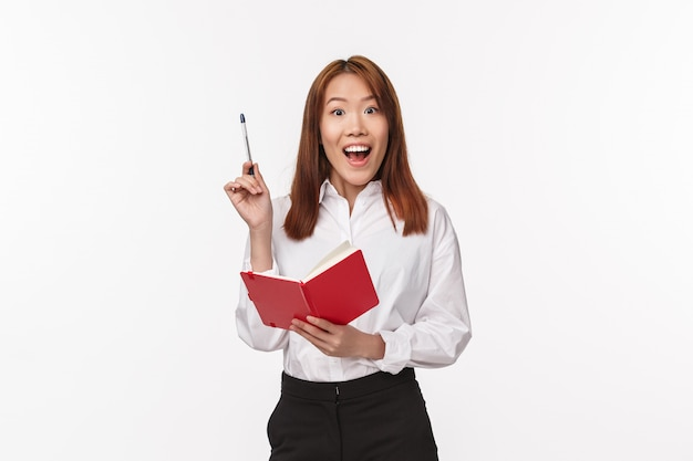 Portrait of excited asian woman in white shirt, hold red notebook raise pen in eureka gesture, gasping wondered and smiling, have great idea, creative plan writing it down, white wall