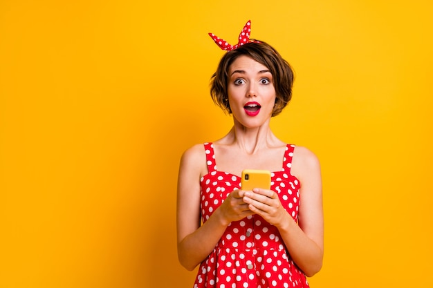 Portrait excited astonished girl use cellphone get incredible social network notification impressed scream wow omg wear red polka-dot retro skirt isolated bright shine color wall
