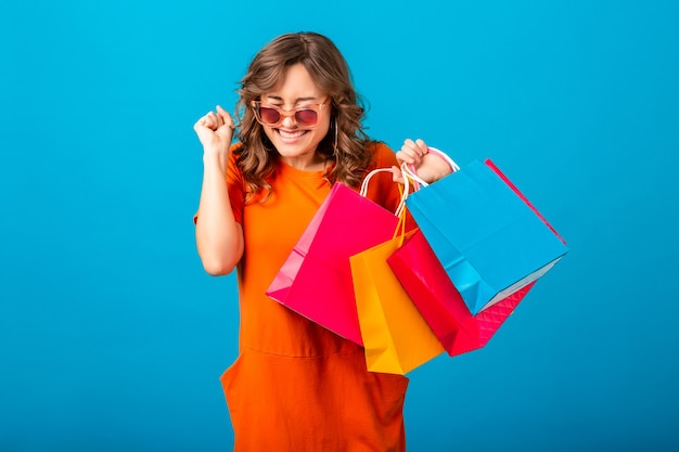 Portrait of excited attractive smiling stylish woman shopaholic in orange trendy dress holding shopping bags on blue studio background isolated