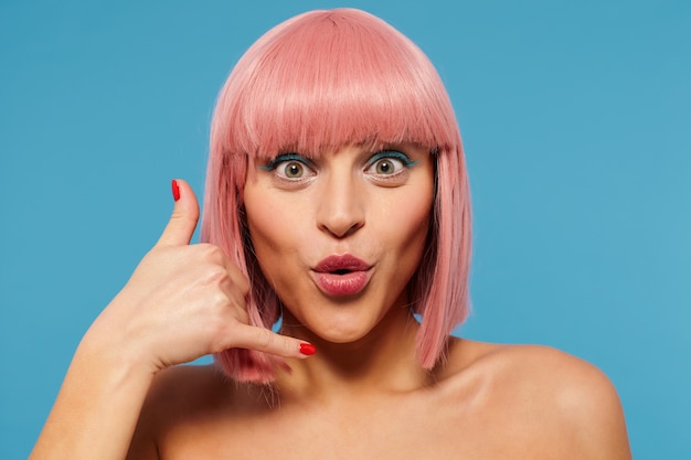 Portrait of excited attractive young pink haired woman with short haircut raising hand in call me gesture while looking at camera with round eyes, standing against blue background