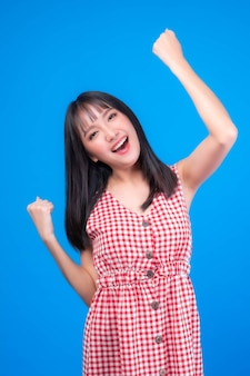 Portrait of excited beautiful asian woman cute girl in red dress with bangs hair style raising hand in the air laughing cheerfully gesturing for winner , smiling , look camera isolated blue background
