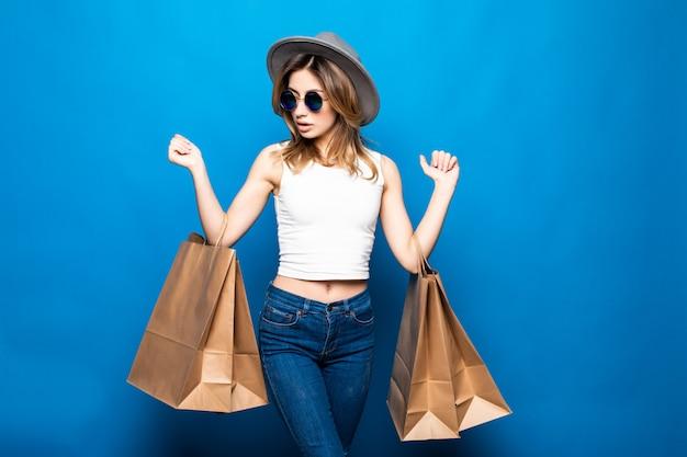 Ritratto di un vestito d'uso e degli occhiali da sole della bella ragazza emozionante che giudicano i sacchetti della spesa isolati sopra la parete blu