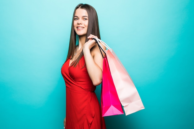 Ritratto di una bella ragazza emozionante che porta vestito rosso e occhiali da sole che tengono i sacchetti della spesa isolati sopra la parete blu