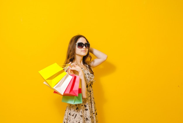 Portrait of an excited beautiful girl with sunglasses holding shopping bags isolated over yellow