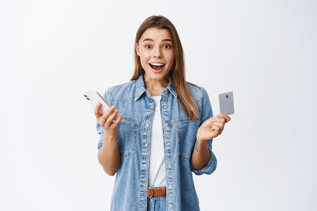 Portrait of excited blond girl shopping online on smartphone, holding credit card and smiling amazed, standing over white wall