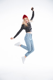 Portrait of an excited blonde young woman in hat jumping with earphones