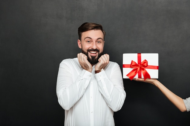 Portrait of excited brunette man rejoicing to get white gift box with red bow from female hand over dark gray wall