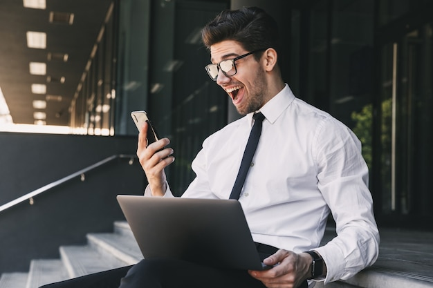Portrait of excited businessman dressed in formal suit sitting outside glass building with laptop, and holding smartphone