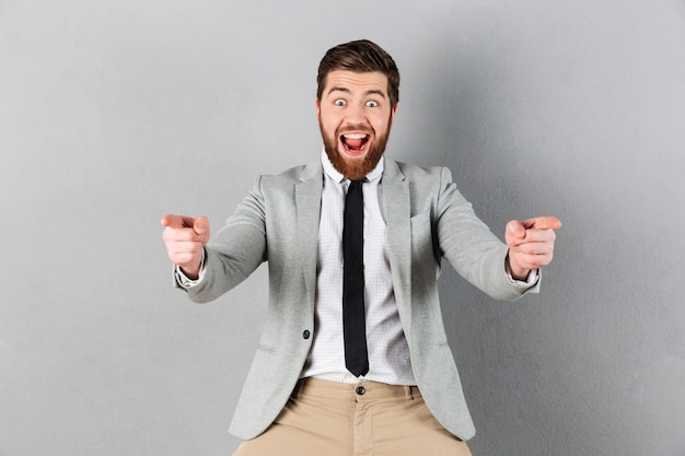 Portrait of an excited businessman dressed in suit standing