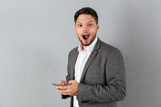 Portrait of an excited businessman holding mobile phone