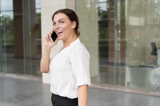Portrait of excited businesswoman talking on smartphone outdoors