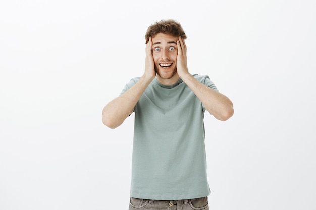 Portrait of excited crazy european guy in t-shirt, holding hands on face and smiling with weird funny expression