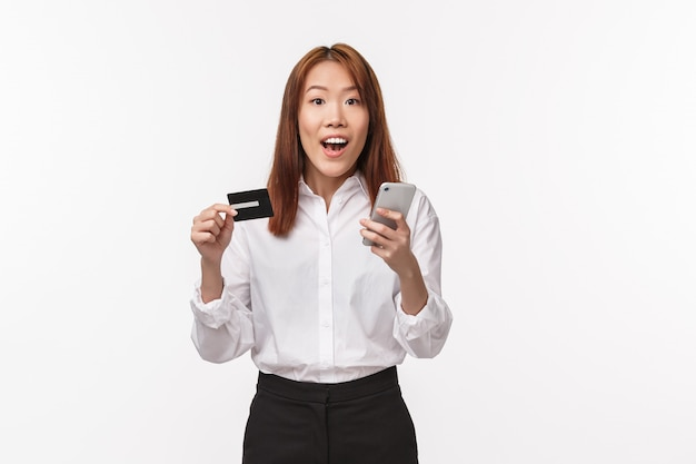 Portrait of excited cute asian female in shirt and skirt, holding mobile phone and credit card, making internet order, shopping online, use bank deposit, register account in store,