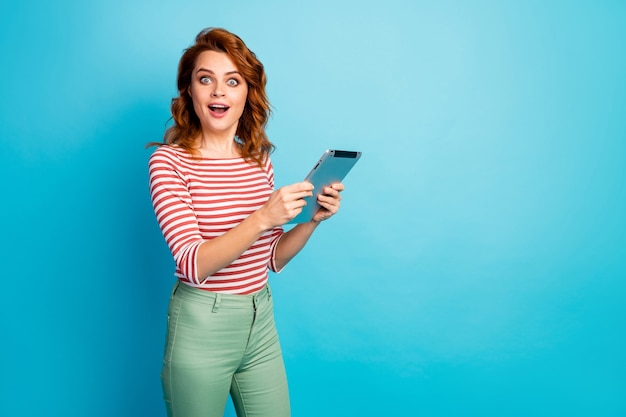Portrait of excited cute sweet girl use tablet search incredible information impressed scream wow omg wear good look shirt isolated over blue color