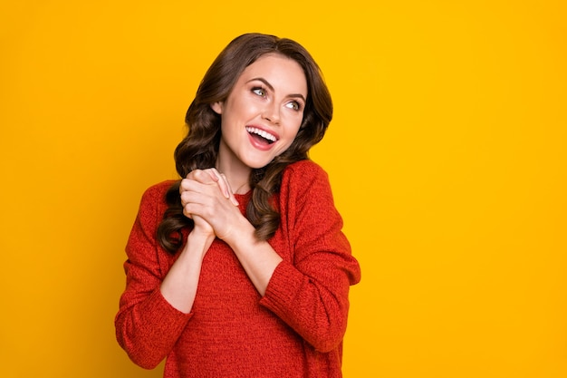 Portrait of excited energetic girl put hands fist together look copyspace enjoy long wait want hope sales ads wear jumper isolated over shine color background
