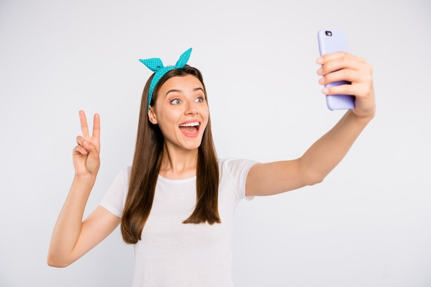 Portrait of excited enthusiastic girl feel positive cheerful emotions take selfie on her smartphone make v-sign greet followers of blog wear white style outfit isolated
