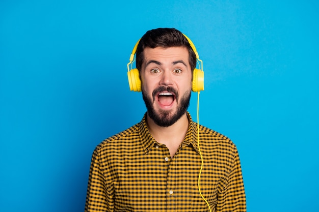 Portrait of excited enthusiastic guy listen radio music find his favorite soundtrack hit impressed scream wow omg wear modern clothing isolated over bright color