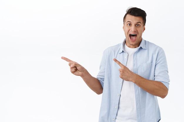 Ritratto di un bell'uomo eccitato ed entusiasta che punta il dito a sinistra e sorride stupito, ha trovato un'eccellente promozione, migliore offerta in stock, sconto speciale basta cliccare sul link, muro bianco