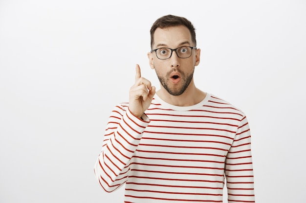 Portrait of excited good-looking guy in black glasses, having idea and raising index finger in eureka gesture