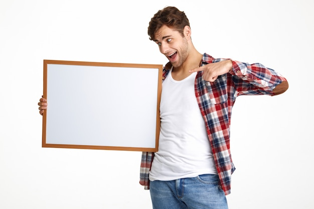 Portrait of an excited guy pointing finger at blank board