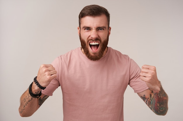 Portrait of excited handsome bearded male with tattooes wearing beige t-shirt and trendy accessories, shouting loud and folding arms in fists while standing on white