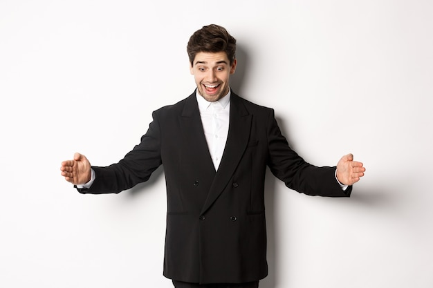 Portrait of excited handsome man in suit, shaping big object on copy space and smiling amazed, holding something, standing over white background