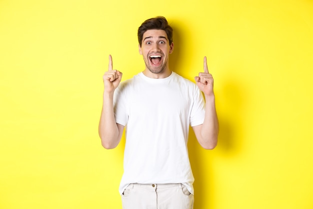 Ritratto di un bell'uomo eccitato con una maglietta bianca, che punta le dita in alto, mostra un'offerta, in piedi su sfondo giallo.
