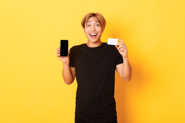 Portrait of excited happy asian man showing mobile phone screen and credit card with joyful smile, standing yellow wall