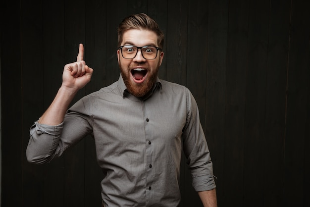 Portrait of a an excited happy bearded man in eyeglasses pointing finger up isolated on the black wooden surface