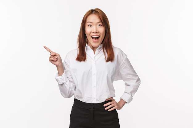 Portrait of excited and happy dreamy asian woman in white shirt, black skirt, open mouth fascinated look camera, pointing finger left at amazing cool new product, want try it,