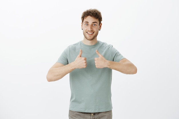 Portrait of excited happy european guy with blond hair in t-shirt, showing thumbs up and smiling broadly, being glad receive excellent idea