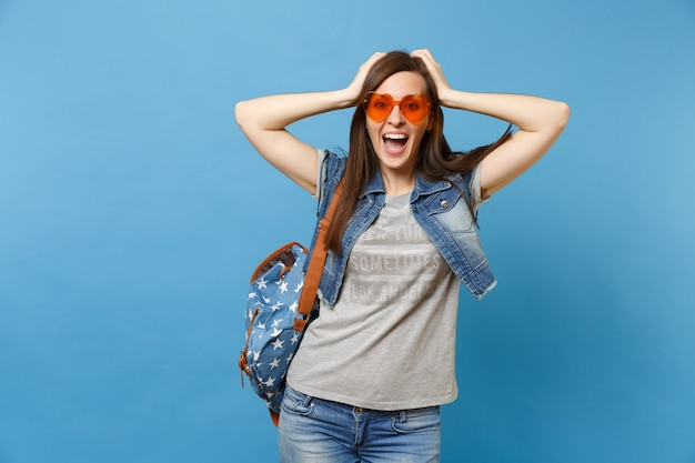 Portrait of excited happy joyful woman student with backpack in denim clothes orange heart glasses clinging to head isolated on blue background. education in high school. copy space for advertisement.