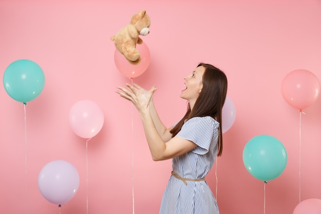 Portrait of excited happy young woman wearing blue dress throwing teddy bear plush toy on pastel pink background with colorful air balloons. birthday holiday party, people sincere emotions concept.