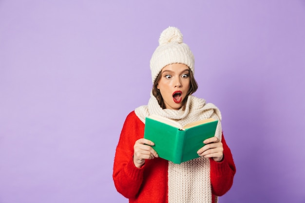 Portrait of an excited happy young woman wearing winter hat isolated over purple wall reading book.