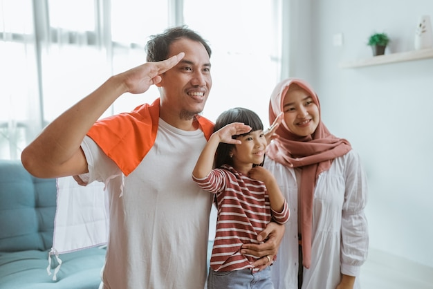 Portrait of excited indonesian family supporter giving salute to camera
