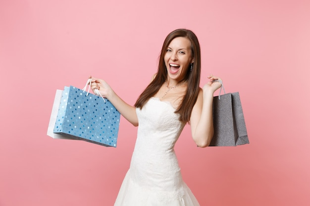 Portrait of excited joyful woman in lace white dress holding multi colored packages bags with purchases after shopping