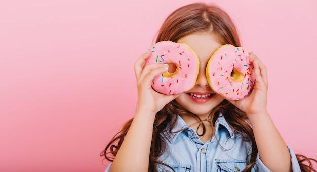 肖像画は、ピンクの背景に分離された目のドーナツとカメラに楽しんで、積極性を表現する青いシャツを着てうれしそうな若いきれいな女の子を興奮させた。おいしいデザートで幸せな子供時代。テキストを配置する
